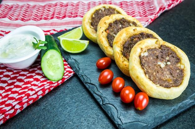 Pyszne libańskie jedzenie, autentyczne sfihas na talerzu łupkowym z pomidorami, cytrynami i tzaztiki.