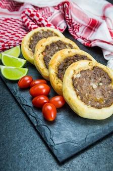 Pyszne libańskie jedzenie, autentyczne sfihas na talerzu łupkowym z pomidorami i cytrynami.
