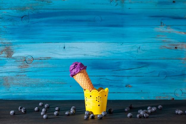 Pyszne lody jagodowe na starej drewnianej niebieskiej ścianie