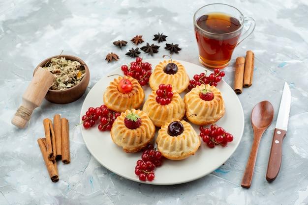 Pyszne małe ciasteczka z widokiem z góry na białym talerzu z wiśniami i truskawkami wraz z cynamonem i herbatą na lekkim biurku ciasto owocowe jagodowe