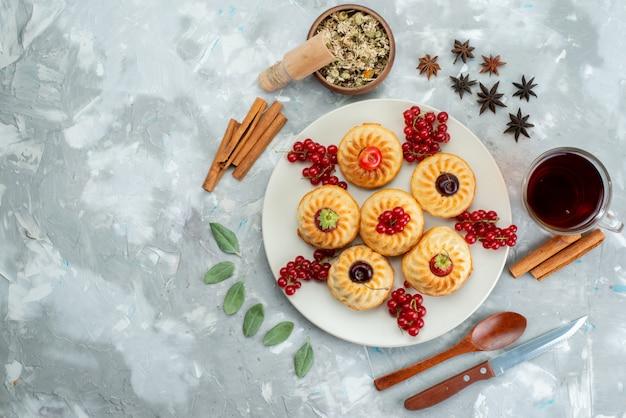Pyszne małe ciastka z widokiem z góry na białym talerzu z wiśniami i truskawkami wraz z cynamonem i herbatą na lekkim biurku ciasto owocowe