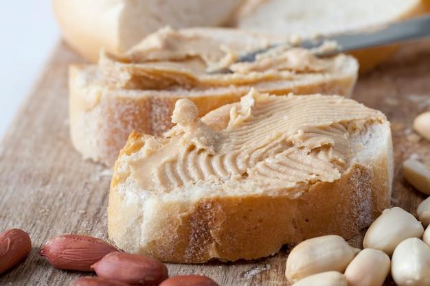 Pyszne masło orzechowe i biały chleb na stole, składniki do przygotowania szybkiego śniadania z chleba i orzeszków ziemnych, pasta orzechowa prażone orzeszki ziemne