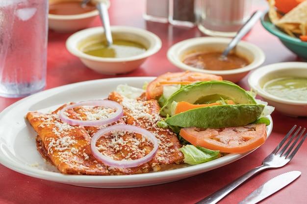 Pyszne meksykańskie roladki z jajek sadzonych z sałatą, awokado, cebulą i pomidorami