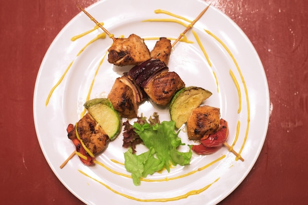 Pyszne mięso wieprzowe i warzywa pokrojone na drewnianych patyczkach mieszają grillowane mięso na białym talerzu