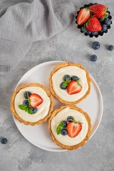 Pyszne mini tarty ze świeżymi jagodami i kremem na białym talerzu