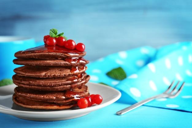Pyszne naleśniki czekoladowe z kaliną na niebieskim drewnianym stole