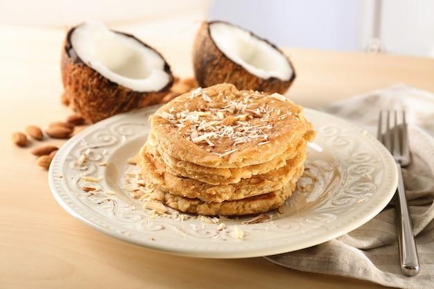 Pyszne naleśniki kokosowe udekorowane wiórkami migdałów na stole