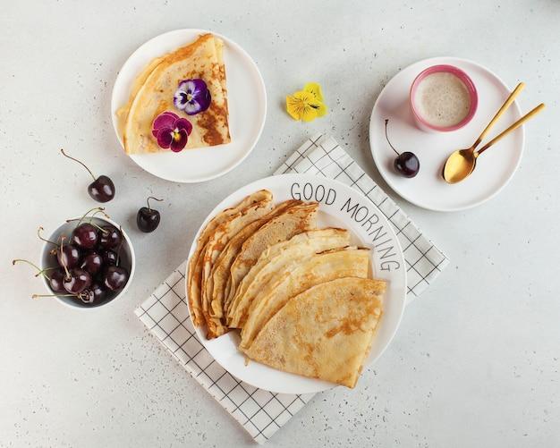 Pyszne naleśniki na talerzach, ozdobione kwiatami i jagodami, kubek do kawy. koncepcja śniadanie, dzień dobry.