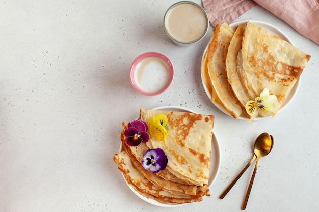 Pyszne naleśniki na talerzach, ozdobione kwiatami i kubkami do kawy
