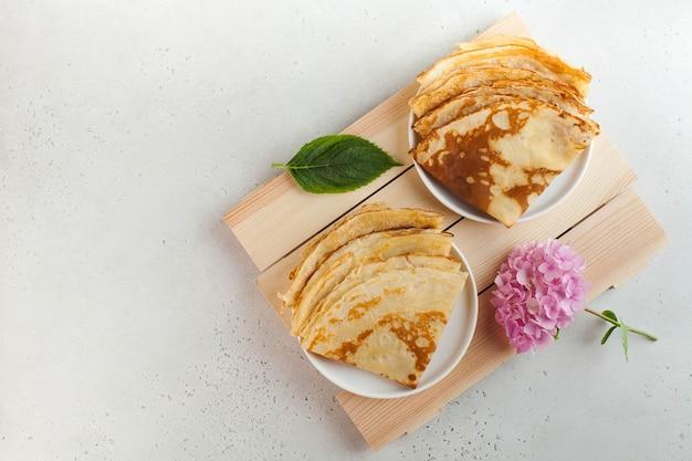 Pyszne naleśniki na talerzu z kwiatami. śniadanie, deser, przepis, kuchnia francuska… maslenitsa