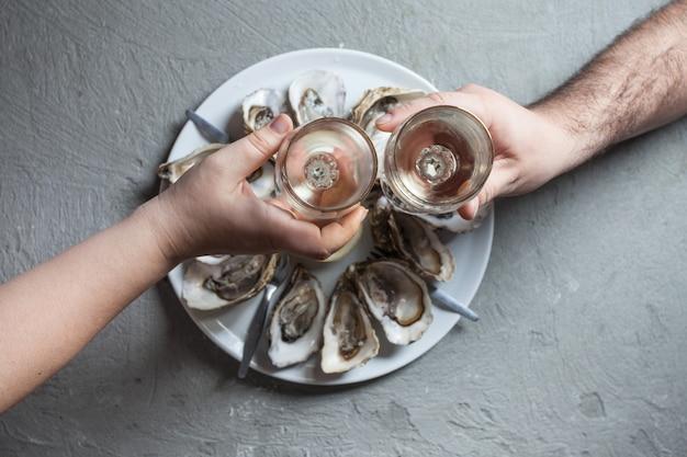 Pyszne ostrygi z plasterkiem cytryny i kieliszkami białego wina, widok z góry