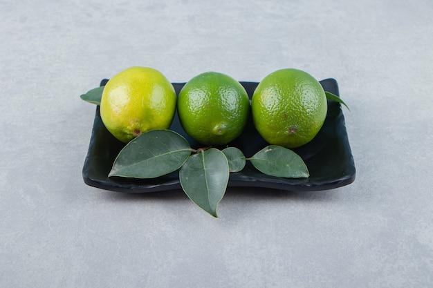 Pyszne owoce limonki na czarnym talerzu