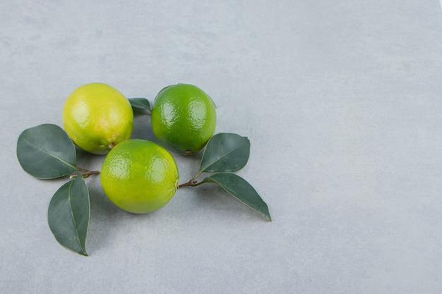 Pyszne owoce limonki z liśćmi na kamiennym stole.