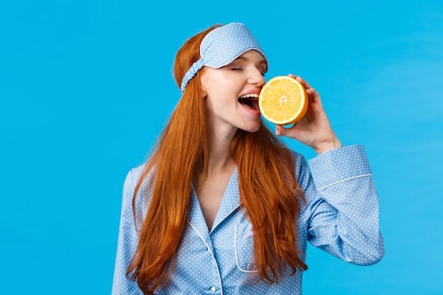 Pyszne owoce od rana zdrowe. portret w talii atrakcyjna śpiąca, ładna ruda dziewczyna w masce i nocnej snu, gryzący kawałek pomarańczy jedzący smacznie, stojący niebieska ściana