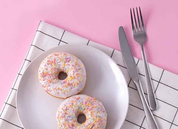 Pyszne pączki na talerzu z serwetką i sztućcami na różowo