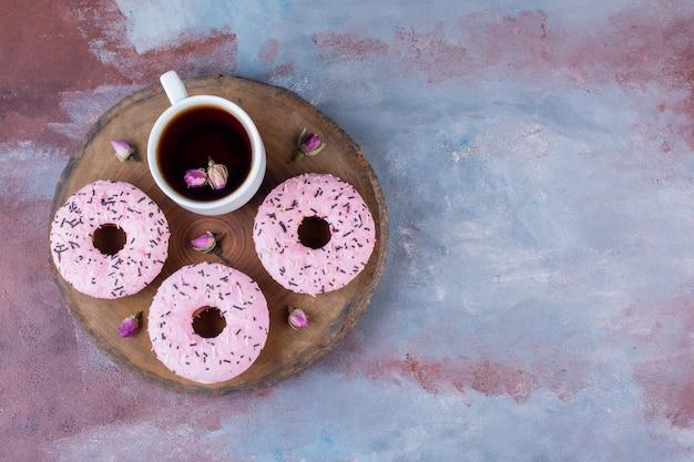 Pyszne pączki z różowym lukrem i filiżanką czarnej herbaty