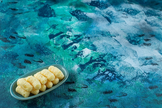 Pyszne paluszki kukurydziane w talerzu, na niebieskim stole.