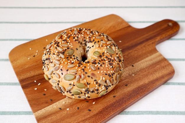 Pyszne pestki słonecznika i pestki dyni z bułką sezamową na drewnianej tablicy chlebowej
