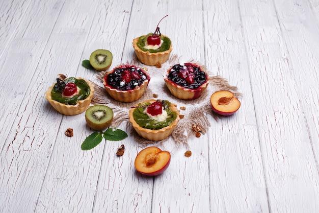 Pyszne pieczone koszyki z owocami, owocami egzotycznymi, zielenią i orzechami