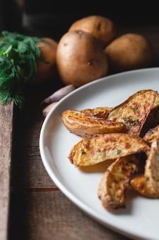Pyszne pieczone ziemniaki wiejskie w dużym białym talerzu z przyprawami, koperkiem i zieloną cebulą na drewnianym stole, widok z góry
