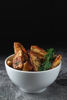 Pyszne pieczone ziemniaki wiejskie z koperkiem i przyprawami w białej misce na ciemnym kamiennym stole