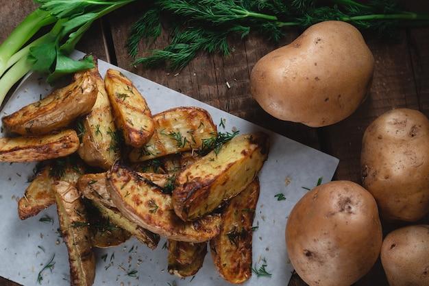 Pyszne pieczone ziemniaki wiejskie z przyprawami, koperkiem i zieloną cebulą na drewnianym stole, widok z góry