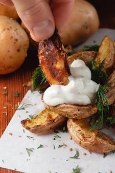 Pyszne pieczone ziemniaki wiejskie z sosem koperkowo-śmietanowym na drewnianym stole