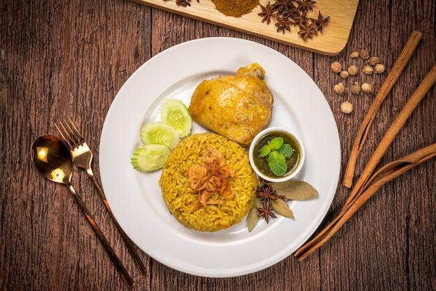 Pyszne pikantne biryani z kurczaka na rustykalnym drewnianym stole, kurczak biryani po tajsku.