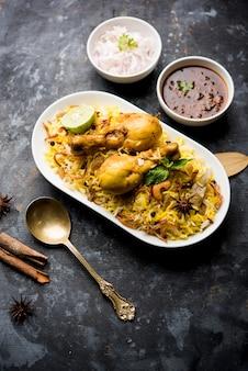 Pyszne pikantne biryani z kurczaka w misce na nastrojowym tle, to popularne indyjskie i pakistańskie jedzenie