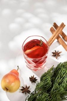 Pyszne pikantne, gorące grzane czerwone wino z cynamonem, anyżem i plasterkiem gruszki podawane w karafce i kieliszku na mroźny zimowy wieczór lub świąteczny napój bożonarodzeniowy