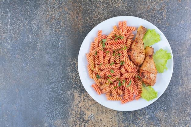 Pyszne podudzia z kurczaka i makaron na białym talerzu. zdjęcie wysokiej jakości