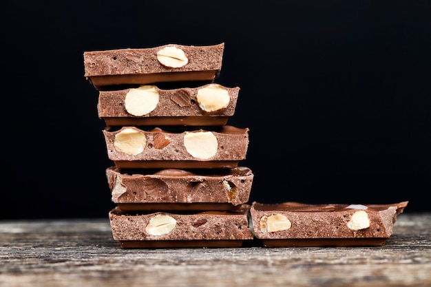 Pyszne prażone migdały i duże kawałki czekolady na drewnianym stole, zbliżenie naturalnych produktów kakaowych z dodatkiem cukru