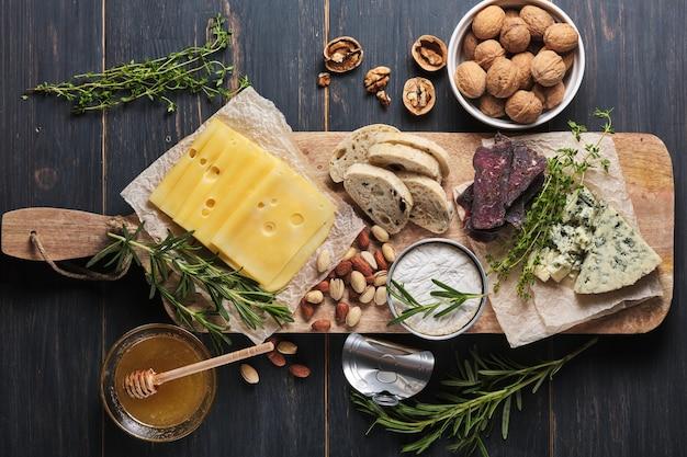Pyszne przekąski. kilka odmian sera, orzechów, ciabatty i kiełbasy na starym drewnianym stole