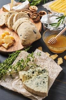 Pyszne przekąski. kilka odmian sera, precli, orzechów i kiełbasy na starym drewnianym stole.