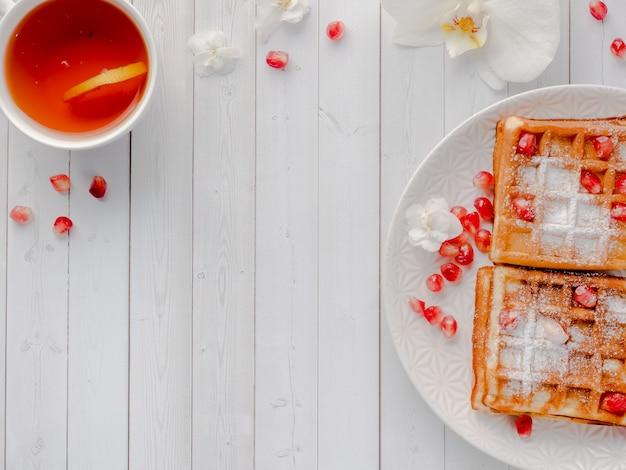 Pyszne przepyszne wiedeńskie gofry z miodem i pestkami granatu na białym talerzu