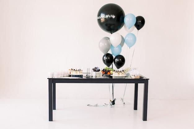 Pyszne przyjęcie urodzinowe. tort urodzinowy, owoce i desery na balony tło wystrój strony. skopiuj miejsce koncepcja uroczystości. modne ciasto. batonik. stół ze słodyczami, cukierkami, deserem.