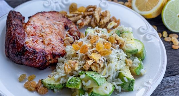 Pyszne risotto z cukinii z warzywami, rodzynkami, orzechami i tartym serem. z pieczonym filetem wieprzowym doprawionym solą, pieprzem i cytryną.