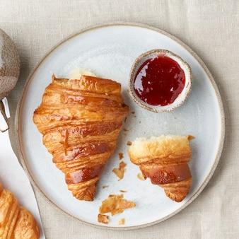 Pyszne rogaliki na talerzu, gorący napój w kubku. rano francuskie śniadanie ze świeżymi wypiekami