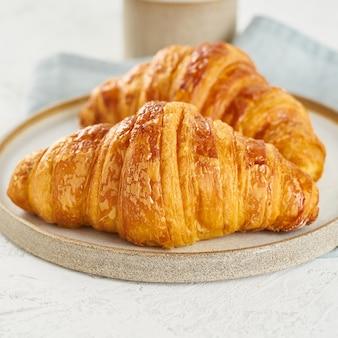 Pyszne rogaliki na talerzu i gorący napój w kubku. rano francuskie śniadanie ze świeżymi wypiekami