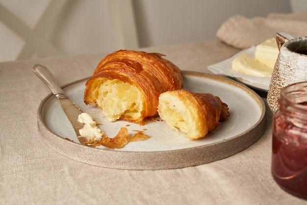 Pyszne rogaliki na talerzu i gorący napój w kubku. rano francuskie śniadanie