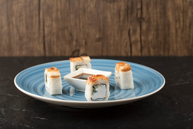 Pyszne rolki smoczego sushi i sos sojowy na niebieskim talerzu