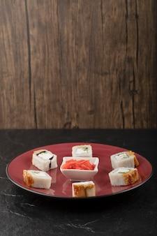 Pyszne rolki smoczego sushi z węgorzem i marynowanym imbirem na czerwonym talerzu