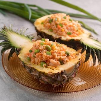 Pyszne, rzeźbione ananasy podawane jako miski w pojemnikach nadziewanych świeżym ananasem, sosem pomidorowym, owocami morza i smażonym ryżem