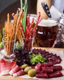 Pyszne salami, kawałki pokrojonej szynki i kiełbaski na tacy. zbliżenie