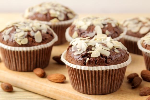 Pyszne, słodkie babeczki czekoladowe, z płatkami migdałów obok orzechów migdałowych na naturalnym drewnianym stole. zbliżenie