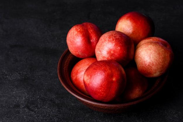 Pyszne słodkie brzoskwinie lub nektarynki w brązowej misce