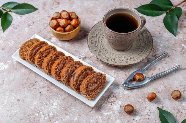 Pyszne słodkie ciasto czekoladowe rolki z kremem z orzechów laskowych i orzechów laskowych, widok z góry