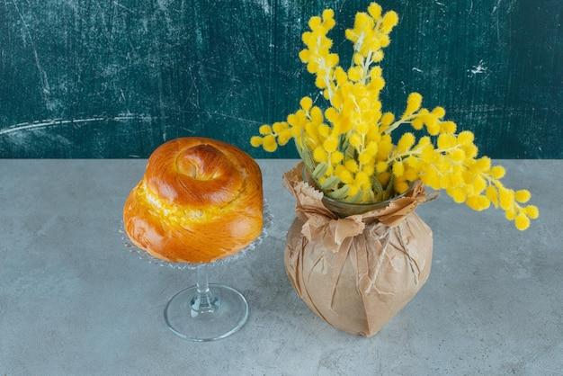 Pyszne słodkie ciasto i żółte kwiaty na marmurze.