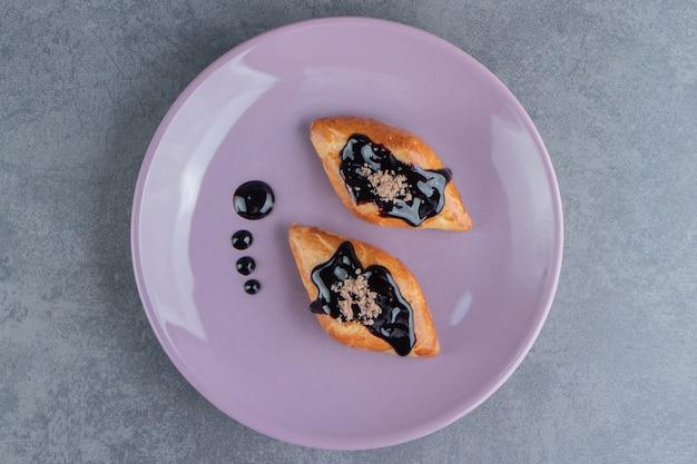 Pyszne słodkie ciasto trójkątne na fioletowym talerzu