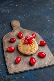 Pyszne słodkie ciasto z czerwonymi dereniami na ciemnoszarym owocowym ciastku jagodowym